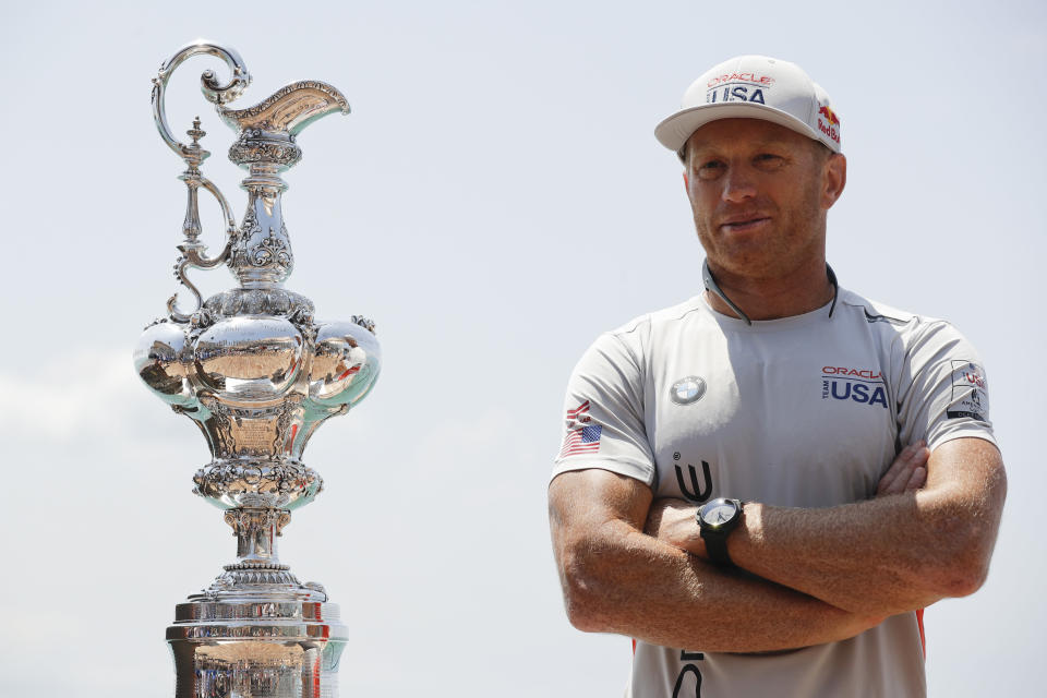 """FILE - In this June 16, 2017, file photo, Oracle Team USA skipper and helmsman Jimmy Spithill stands alongside the America's Cup trophy, known as the """"Auld Mug,"""" before a news conference in Hamilton, Bermuda. Spithill has signed on as CEO and helmsman of the United States team in SailGP, giving the global league another former America's Cup champion in its stable of stars. (AP Photo/Gregory Bull, File)"""