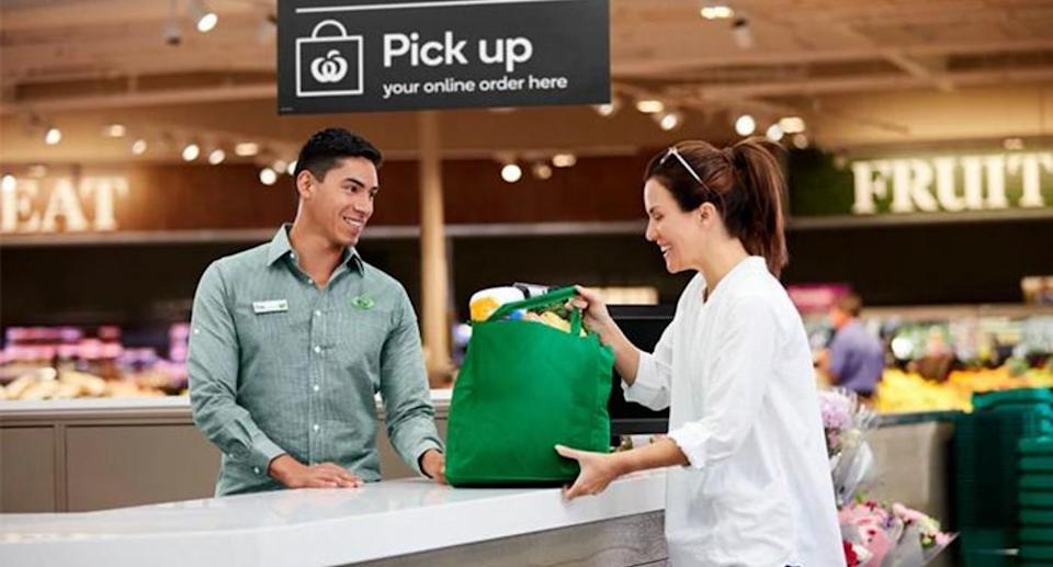 Woolworths staff member hands shopper a bag. Source: Woolworths Group