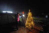 Tiffany Theriot, right, founder of the charity Cajun Commissary, surprises Cristin Trahan with a Christmas tree donated by a volunteer, on the property of their destroyed home in Lake Charles, La., Friday, Dec. 4, 2020. Cristin, her husband and a son are living in tents on the property, while her other son, his fiancée and their one-year old son are living in a loaned camper there. A relative's home on the same property is now gutted and they are living in a camper as well. (AP Photo/Gerald Herbert)
