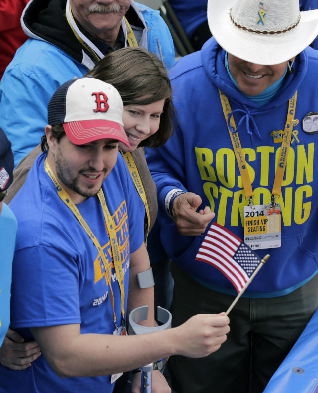 Boston Marathon bombing survivor Jeff Bauman waves an American flag alongside his fiancee Erin Hurley and Carlos Arredondo, right, the cowboy hat-wearing spectator who was hailed as a hero for helping the wounded after the bombings, near the finish line of the 118th Boston Marathon Monday, April 21, 2014 in Boston. (AP Photo/Charles Krupa)