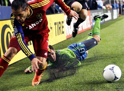 Seattle Sounders' Christian Tiffert (13) goes down out of bounds as he battles Real Salt Lake's Fabian Espindola, left, for the ball in the second half of an MLS soccer match Wednesday, Oct. 17, 2012, in Seattle. The teams played to a 0-0 tie. (AP Photo/Ted S. Warren)
