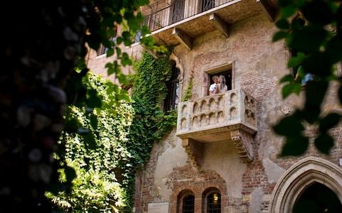"For the lovelorn and incurably romantic, it is a staple of any visit to Verona – the Gothic palazzo where Shakespeare purportedly imagined his Juliet to have lived, including a balcony from where she was wooed by Romeo. The Bard's ""star-cross'd lovers"" may have been fictional, but that does not stop tourists from around the world from leaving sentimental notes and scrawling their names on the brick walls of the palazzo's courtyard. The custom of leaving love messages, many of them addressed to Shakespeare's heroine, was celebrated in a 2010 film, Letters to Juliet, starring Vanessa Redgrave and Amanda Seyfried. But the graffiti is now spreading beyond Juliet's House, or La Casa di Giulietta as it is known in Italian, onto the street outside, to the exasperation of locals. Shopfronts along Via Cappello, outside the entrance to the historic property, are now plastered in unsightly graffiti, love messages and tourists' names, much of it written in indelible ink. A signpost outside Juliet's House in Verona is all but obscured by stickers and graffiti Credit: Alamy Some visitors have taken to writing their initials on padlocks, bolting them to shop fronts and throwing away the keys, a trend long-established in cities such as Rome and Paris, where thousands of rusting padlocks have to be removed from bridges and monuments each year. ""A lot of tourists are badly behaved and think they have the right to scrawl graffiti all over the place. When I catch them with a pen in their hand and tell them to stop, they get angry with me, even though it should be the other way around,"" said Davide Albertini, the owner of a fashion shop a few yards from the entrance to Juliet's House. ""We spent a large amount of money last December to clean up the graffiti but a year on, it's worse than ever,"" he told The Telegraph. Mr Albertini and other business owners have written to Verona city council asking for more surveillance of the area by local police. ""We want to collaborate with the authorities to maintain decorum in the city centre,"" he said. A couple kisses on the balcony of Juliet's House in Verona Credit: Getty In 2008, the city introduced fines of up to €500 (£445) for anyone caught writing graffiti on public or private property, but the penalties are rarely enforced. Like Venice and Florence, which also struggle to manage the effects of mass tourism, Verona is a victim of its own success, attracting an estimated two million visitors a year, the majority of whom want to see Juliet's House, a former medieval inn. It is not just graffiti that has become a problem. A bronze statue of Juliet had to be removed from the courtyard of the house because so many tourists had taken to rubbing its right breast in the hope of bringing good luck. Business owners in Verona are alarmed by the spread of graffiti around Juliet's House, one of Verona's most popular attractions Credit: Brian Harris/Alamy A crack appeared in the breast from all the wear and tear, and damage was done to the statue's right arm, which tourists leant on as they had their photos taken. ""The condition of the sculpture was undermined by the contact of so many tourists, particularly the tradition of touching Juliet's right breast,"" the guardians of Juliet's House said at the time. The bronze had stood in the courtyard since 1972 but was removed in 2014 and replaced by an exact replica created by a local foundry. The original was placed inside a museum within Juliet's House. ""The small hole that remains visible in the breast is a record of the service rendered by the old Juliet for more than 40 years to the lovelorn of the whole world,"" the custodians said."
