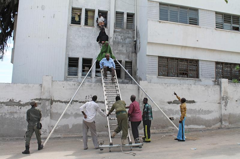 Survivors are helped to escape from a window at Mogadishu's court complex in Mogadishu, Somalia, Sunday, April 14, 2013. Militants launched a serious and sustained assault on Mogadishu's main court complex Sunday, detonating at least two blasts, taking an unknown number of hostages and exchanging extended volleys of gunfire with government security forces, witnesses said.(AP Photo/Farah Abdi Warsameh)