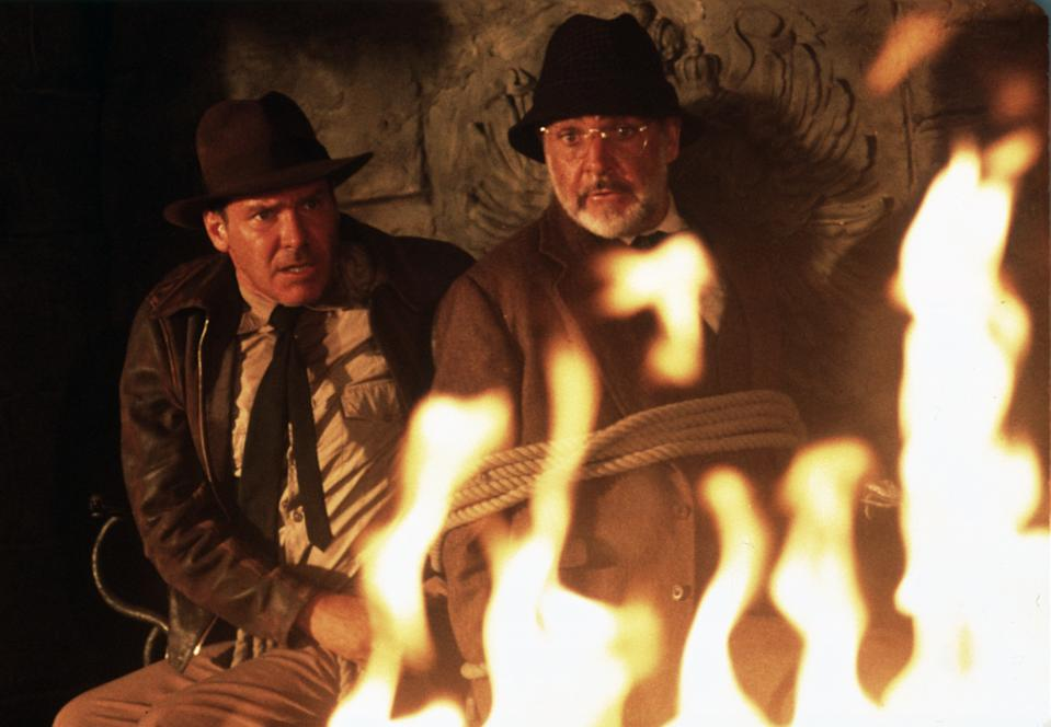 American actor Harrison Ford as the eponymous archaeologist and Scottish actor Sean Connery as his father Henry Jones in a scene from the film 'Indiana Jones and the Last Crusade', 1989. Here the two are trapped in a Nazi stronghold.  (Photo by Murray Close/Getty Images)
