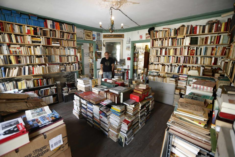 Bookseller Nicolas Mahieu poses inside his bookshop in Goussainville-Vieux Pays. Days go by without a customer in his over-stocked shop, but he supports himself by selling over the internet. (Reuters)