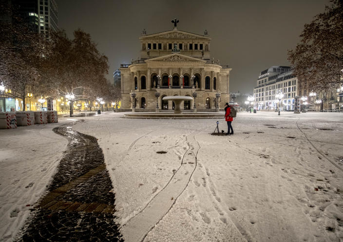 A woman takes pictures of the Old Opera in Frankfurt, Germany, after snow falls on Sunday, Jan. 17, 2021. (AP Photo/Michael Probst)