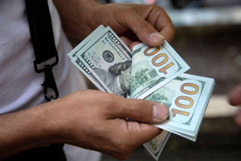 Dollar rises with stocks, investors stay cautious