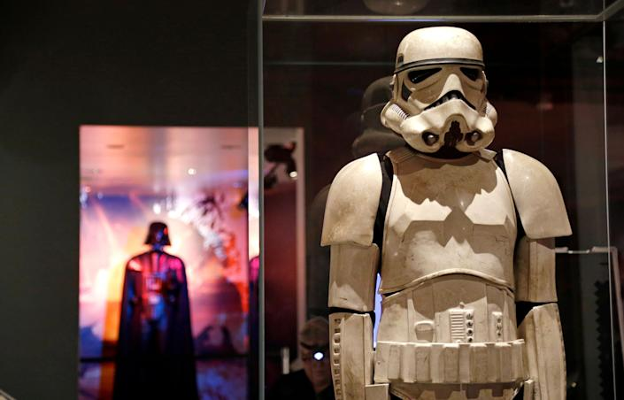 A stormtrooper costume is displayed with Darth Vader behind. (AP Photo/Elaine Thompson)