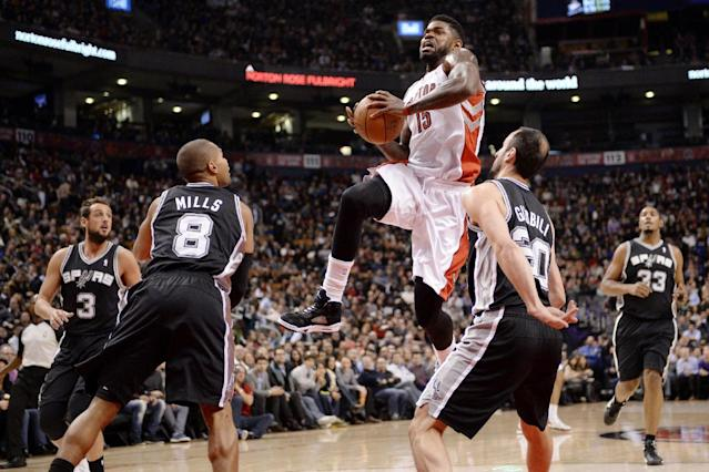 Toronto Raptors forward Amir Johnson (15) drives to the net between San Antonio Spurs guard Manu Ginobli (20) and guard Patty Mills (8) as guard Marco Belinelli (3) and forward Boris Diaw (33) stand by during the first half of an NBA basketball game in Toronto on Tuesday, Dec. 10, 2013. (AP Photo/The Canadian Press, Frank Gunn)