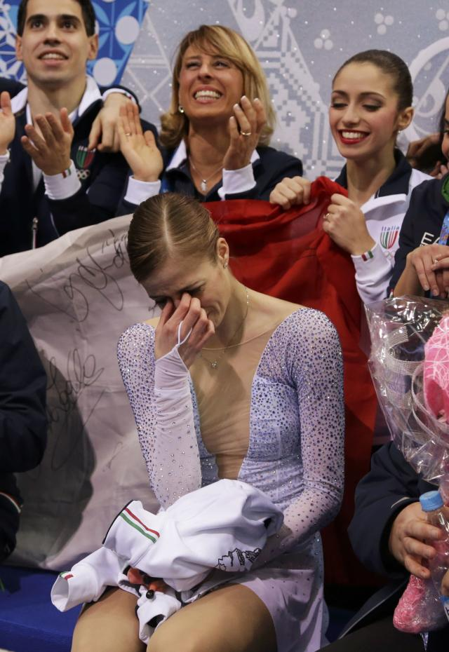 """Carolina Kostner of Italy reacts in the """"kiss and cry"""" area with her teammates during the Team Ladies Short Program at the Sochi 2014 Winter Olympics, February 8, 2014. REUTERS/Darron Cummings/Pool (RUSSIA - Tags: SPORT FIGURE SKATING SPORT OLYMPICS)"""