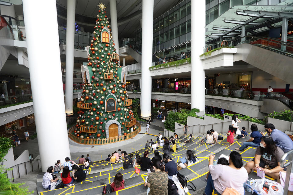 People sitting at designated social distancing areas next to a 20-metre-tall Christmas tree at a shopping mall in Singapore.