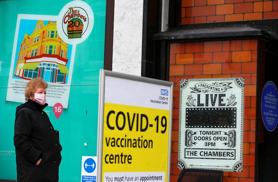 A woman queues to receive the coronavirus disease (COVID-19) vaccine outside a closed down Debenhams store that is being used as a vaccination centre in Folkestone, Kent, Britain January 28, 2021. REUTERS/Andrew Couldridge