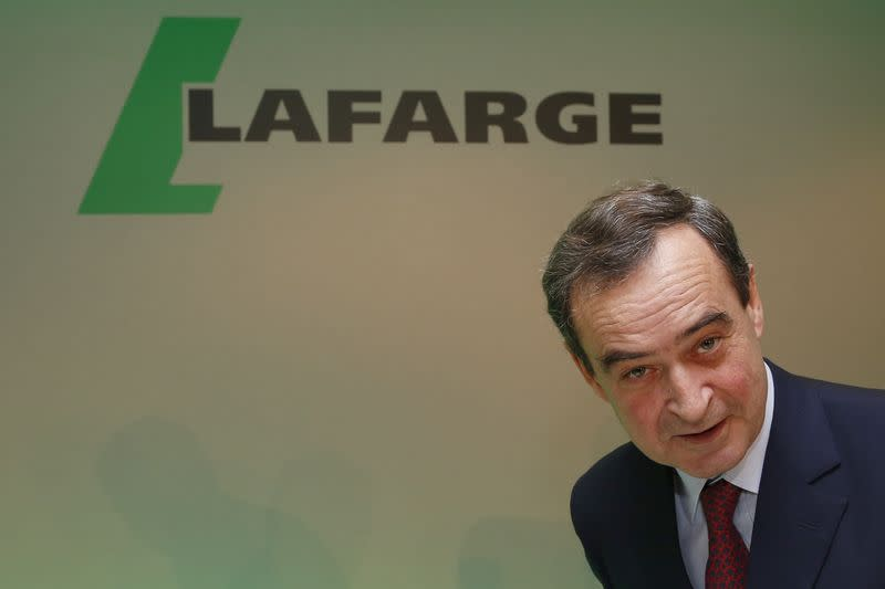 Bruno Lafont, Chairman and CEO of Lafarge, reacts as he takes his seat before announcing the company 2014 anual results at a news conference in Paris