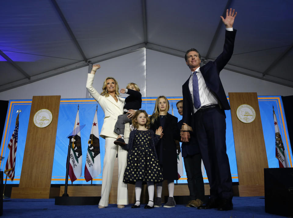 FILE -- In this Jan. 7, 2019 file photo, California Gov. Gavin Newsom, his wife, Jennifer Siebel Newsom, and family waves after taking the oath office during his inauguration as the 40th Governor of California, Sacramento, Calif. With one year left in his first term as the state's chief executive, Newsom is facing the second recall of a California governor in state history. Voters recalled Democrat Gray Davis in 2003 but today's electorate is more favorable for Democrats. (AP Photo/Rich Pedroncelli, File)