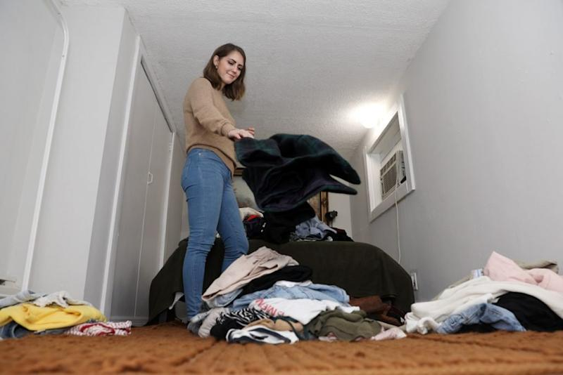 A woman sorts through her closet.