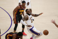 Los Angeles Lakers forward LeBron James, center, grimaces as he trips and injures himself over Atlanta Hawks forward Tony Snell, bottom, during the first half of an NBA basketball game Saturday, March 20, 2021, in Los Angeles. (AP Photo/Marcio Jose Sanchez)