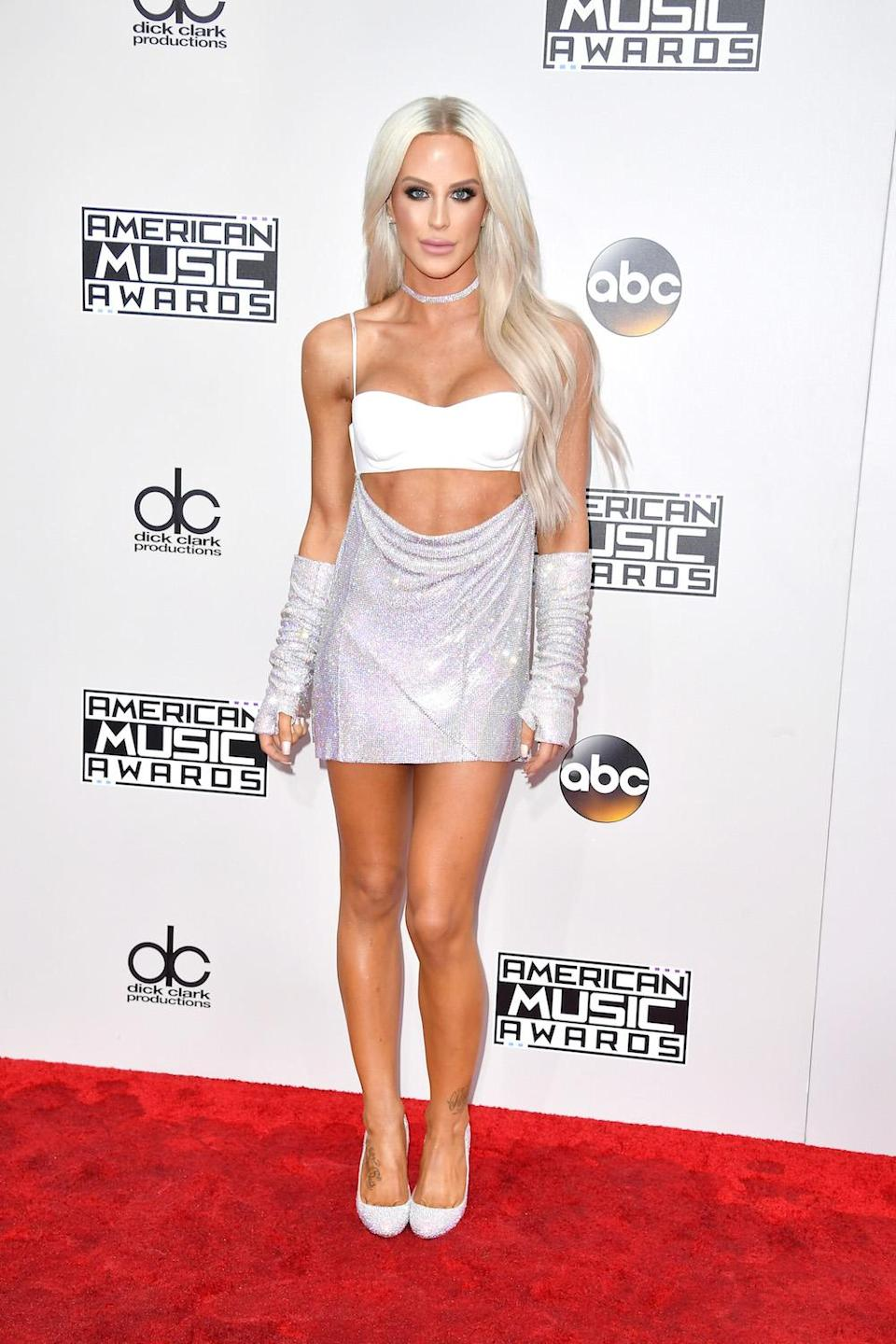 <p>Gigi Gorgeous wore a white bandeau top with an attached glittering skirt that showed off her midriff with matching detached sleeves. <em>(Photo: Getty Images)</em> </p>