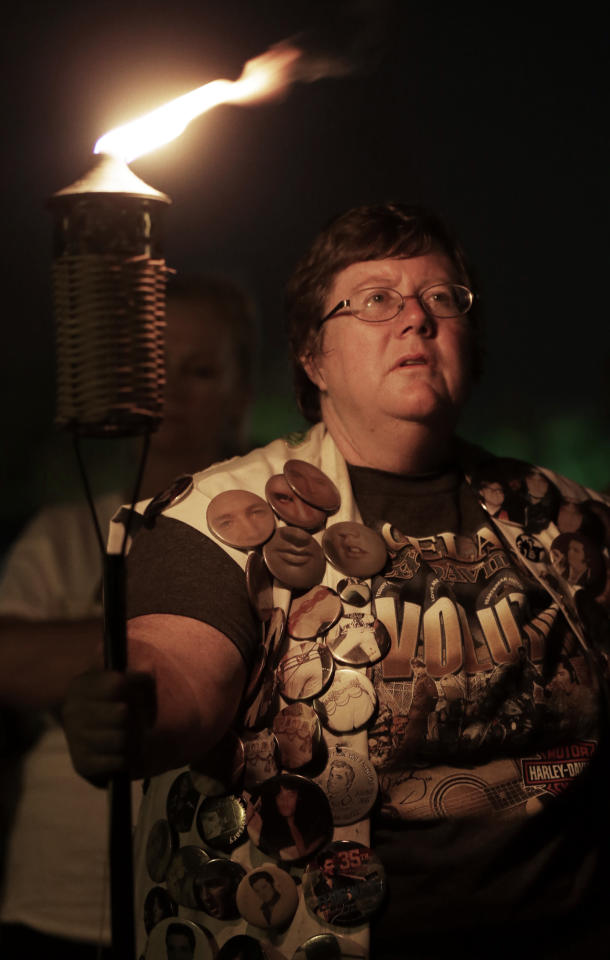 Ann Marie McClain, of Horn Lake, Miss., wears a vest covered with Elvis Presley buttons as she takes part in a candlelight vigil at Graceland, Presley's Memphis, Tenn. home, on Wednesday, Aug. 15, 2012. Fans from around the world are at Graceland to commemorate the 35th anniversary of Presley's death. (AP Photo/Mark Humphrey)