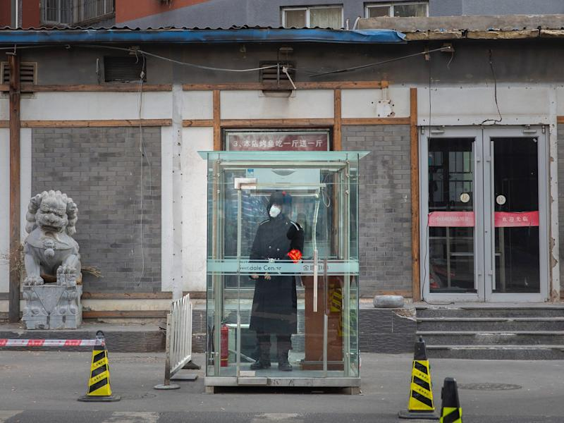Coronavirus, China, security guard in a face mask stands in a glass cubicle on an empty street in Beijing.