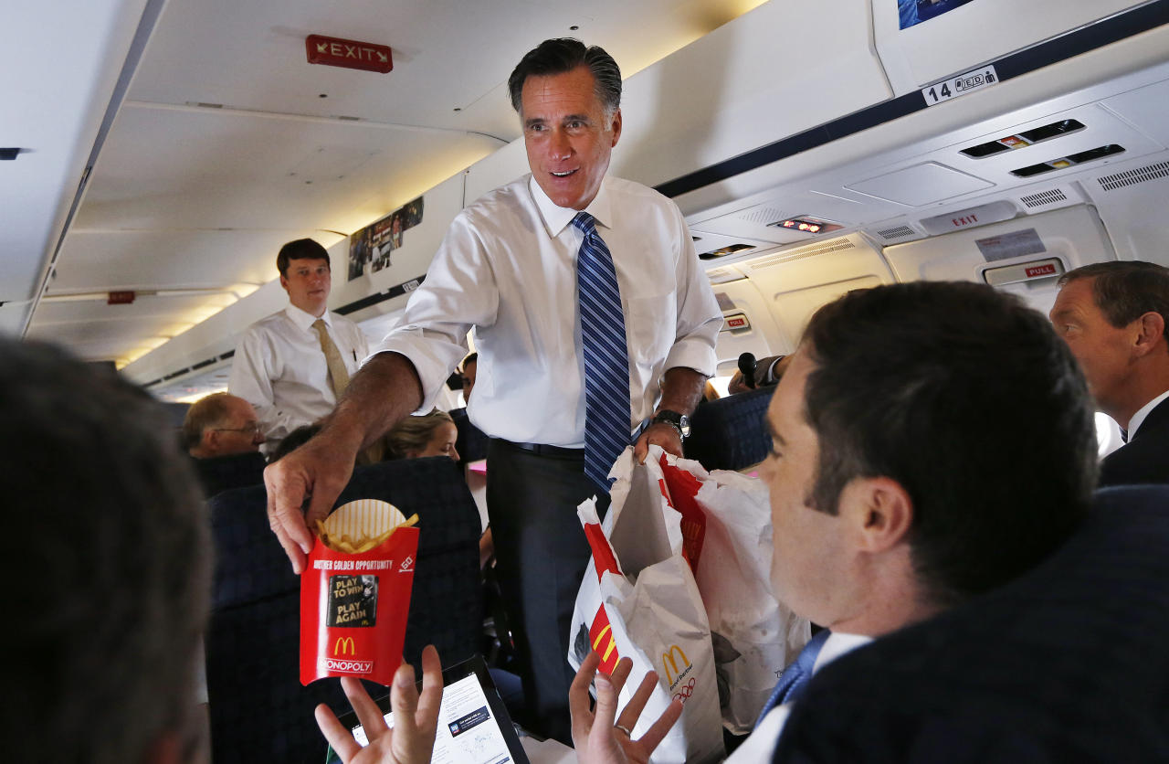 Republican presidential nominee Mitt Romney hands out McDonald's french fries to the media aboard his campaign plane leaving Weyers Cave, Virginia October 8, 2012. REUTERS/Shannon Stapleton (UNITED STATES - Tags: POLITICS ELECTIONS MEDIA TRANSPORT USA PRESIDENTIAL ELECTION)