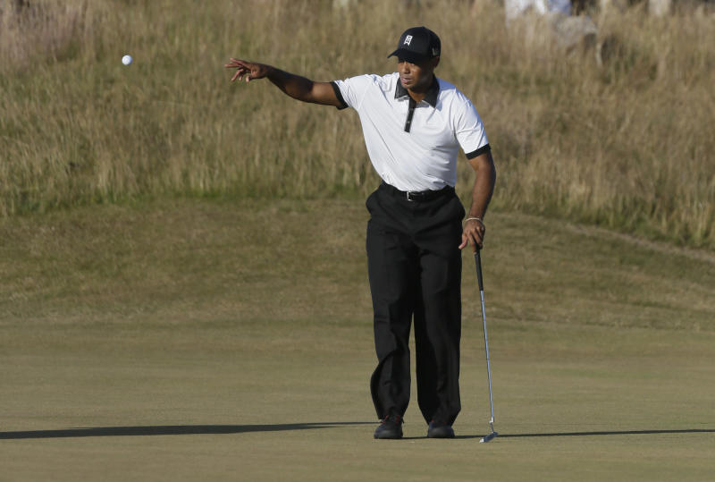 Tiger Woods of the United States catches a ball from his caddie Joe LaCava on the 17the green during the first round of the British Open Golf Championship at Muirfield, Scotland, Thursday July 18, 2013. (AP Photo/Jon Super)