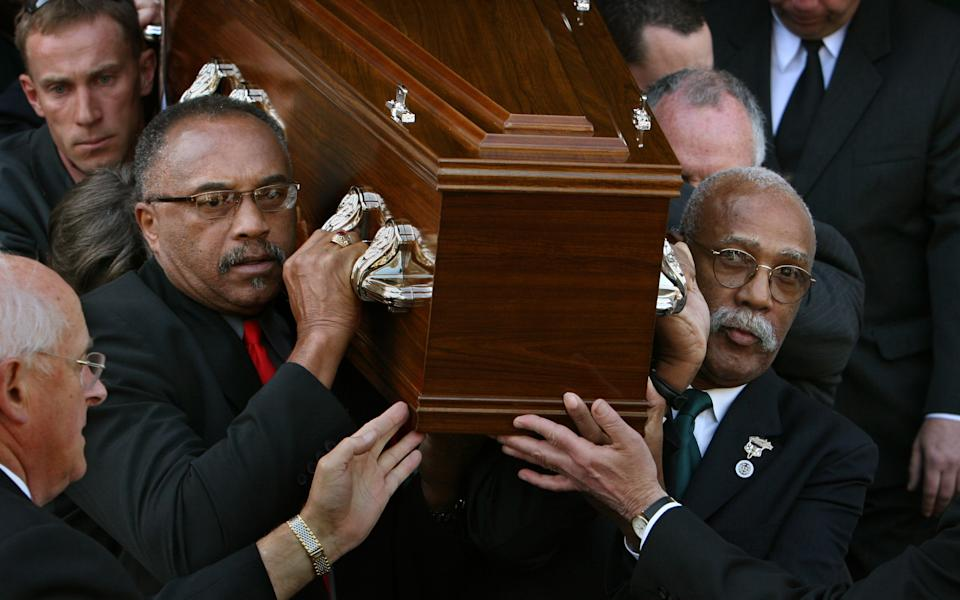 Tommie Smith, (left) and John Carlos carry Peter Norman's casket from the Williamstown Town Hall on 9th October, 2006. (Fairfax Media via Getty Images/Fairfax Media via Getty Images)