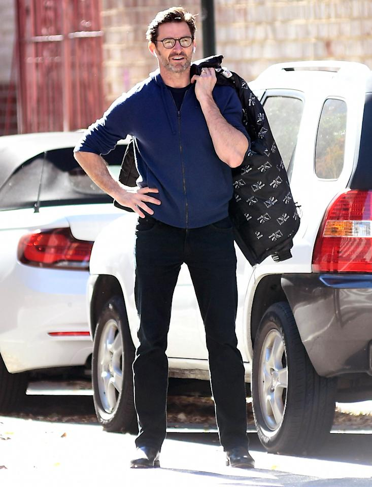 Hugh Jackman takes his coat off as the sun comes out while he waits for a taxi in New York City on Friday.