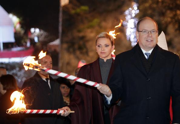 <p>Prince Albert II of Monaco (R) and his wife Princess Charlene (L) of Monaco hold a torch to burn a small fisherman's boat during the traditional Sainte Devote procession in Monaco, on January 26, 2017.<br />Sainte devote is the patron saint of Monaco and France's Mediterranean Corsica island. / AFP / POOL / ERIC GAILLARD (Photo credit should read ERIC GAILLARD/AFP/Getty Images)</p>
