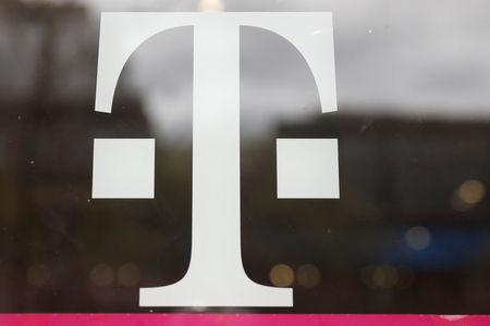 A T-Mobile logo is seen on the storefront door of a store in Manhattan