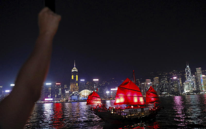 A demonstrator raises their fist at the Tsim Sha Tsui waterfront as a sailing junk passes by during a protest in Hong Kong, Friday, Aug. 23, 2019. Supporters of Hong Kong's pro-democracy movement lined city streets and part of the city's harbor front Friday, inspired by a human chain in a historic Baltic states protest against Soviet control 30 years ago. (AP Photo/Vincent Yu)