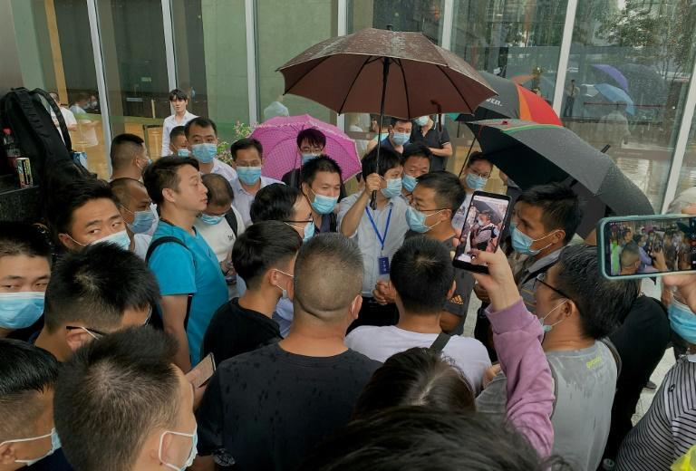 Dozens of anxious protesters gathered outside Chinese conglomerate Evergrande's headquarters in Shenzhen (AFP/Noel Celis)