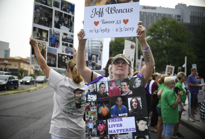 "FILE - In this Aug. 17, 2018, file photo, Lynn Wencus of Wrentham, Mass., holds a sign with a picture of her son Jeff and wears a sign of others' loved ones lost to OxyContin and other opioids during a protest at Purdue Pharma LLP headquarters in Stamford, Conn. Some of the money in Purdue Pharma's proposed multibillion-dollar opioid settlement would come from the continued sale of opioids. ""It's blood money paying for blood money,"" said Wencus. ""It's ludicrous. The whole thing would be almost comical if we weren't talking about human lives here."" (AP Photo/Jessica Hill, File)"