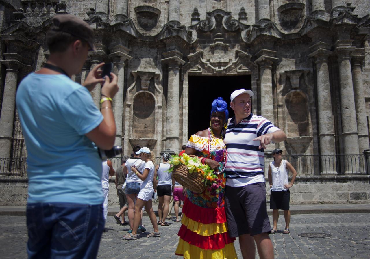 In this picture taken Sept 11, 2012, Russian tourists take pictures of themselves with a Cuban woman dressed in a traditional outfit who takes tips for posing for photos outside the Cathedral in Havana, Cuba. When the Obama administration loosened travel restrictions to Cuba, the thought was that Americans were going to pour into the island on legal cultural exchanges. But several U.S. travel operators complain that, just over a year after the U.S. re-instituted so-called people-to-people exchanges to Cuba, applications to renew their licenses are languishing, forcing cancellations, layoffs and the loss of millions of dollars in revenue. (AP Photo/Ramon Espinosa)