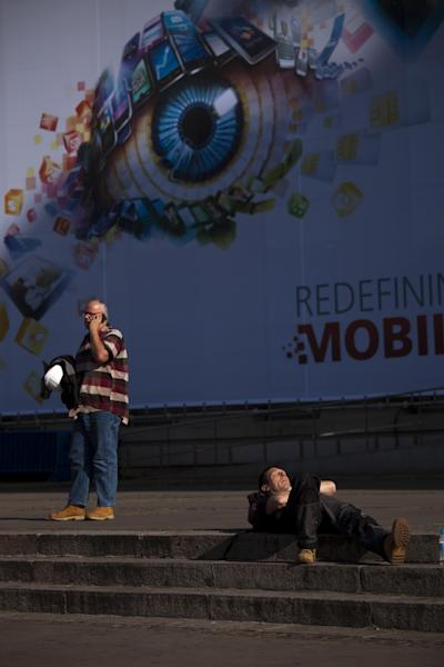 A man sleeps on the ground as other uses his mobile phone next to a big banner announcing the world's largest mobile phone trade show in Barcelona, Spain, Thursday March. 1, 2012. (AP Photo/Emilio Morenatti)