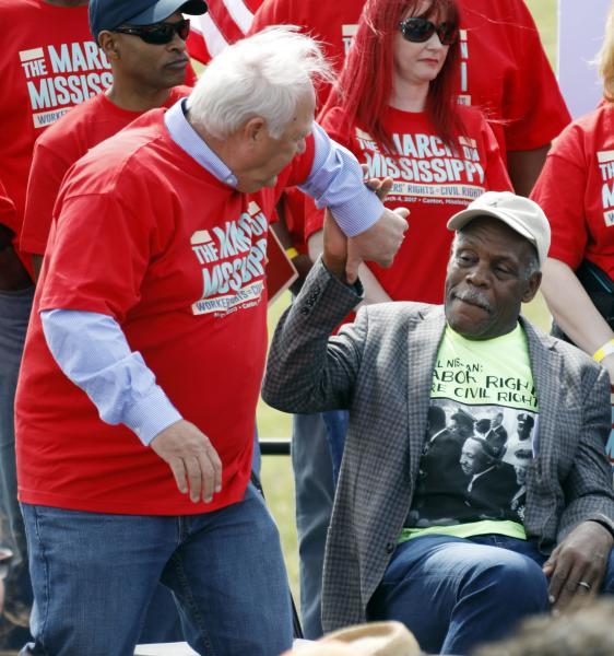 UAW president Dennis Williams, left, is congratulated on his comments by actor Danny Glover at a pro-union rally near Nissan Motor Co.'s Canton, Miss., plant, Saturday, March 4, 2017. Participants marched to the plant to deliver a letter to the company demanding the right to vote on union representation to address better wages, safe working conditions and job security. (AP Photo/Rogelio V. Solis)