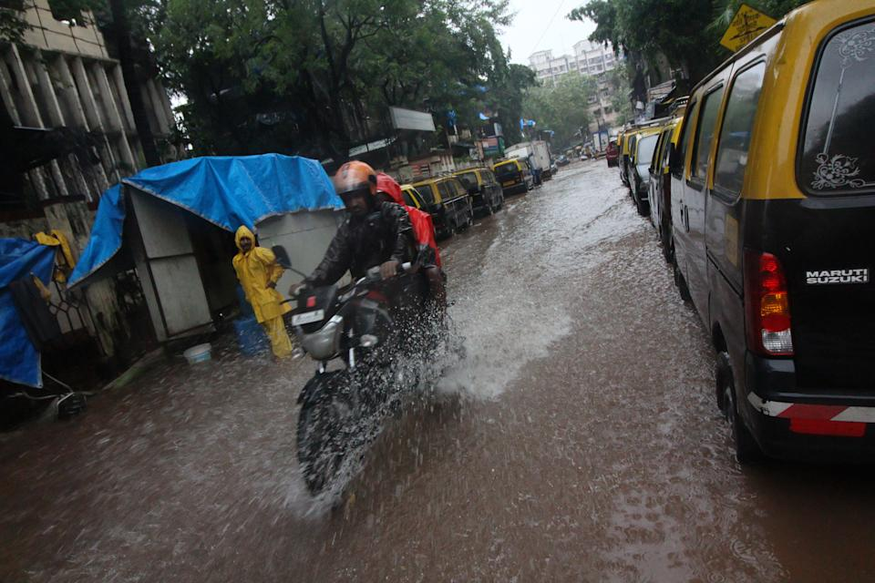 People ride a motorcycle through a flooded road during heavy rains in Mumbai, India on August 05, 2020. (Photo by Himanshu Bhatt/NurPhoto via Getty Images)