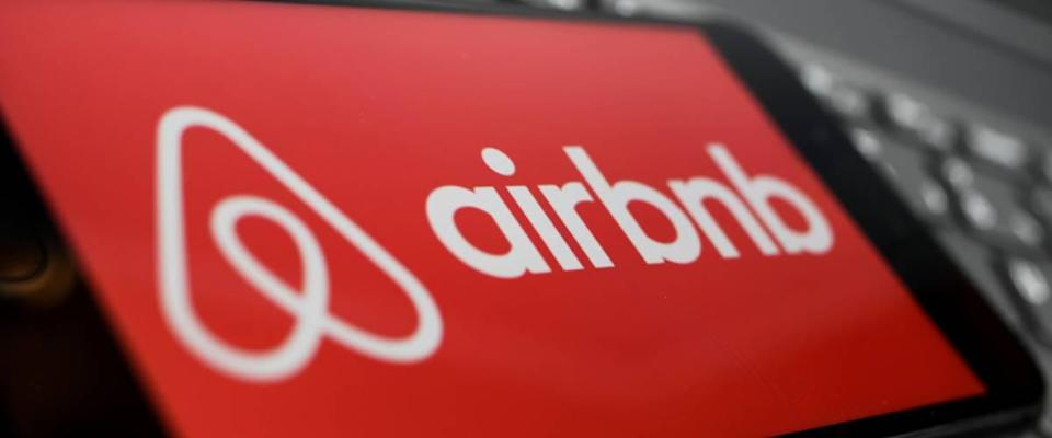 Close up of isolated mobile phone with red airbnb logo lettering on computer keyboard.