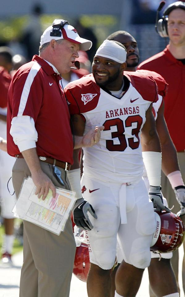 Arkansas football coach Bobby Petrino and running back Dennis Johnson (33) confer during an NCAA college football game against Mississippi Saturday, Oct. 22, 2011, in Oxford, Miss. Arkansas won 29-24. (AP Photo/Rogelio V. Solis)