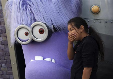 """Girl laughs while standing with a purple Evil Minion character at new """"Despicable Me Minion Mayhem"""" ride during technical rehearsals for new attraction at Universal Studios Hollywood in Universal City, California"""
