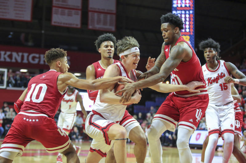Rutgers guard Paul Mulcahy (4) tries to move the ball between Indiana guard Rob Phinisee (10) and forward De'Ron Davis (20) during the first half of an NCAA college basketball game, Wednesday, Jan. 15, 2020 in Piscataway, N.J. (Andrew Mills/NJ Advance Media via AP)