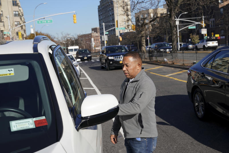 Driver Antonio Rosario gets in his car in front of Super Class Radio Dispatch in the Bronx borough of New York, Tuesday, Nov. 26, 2019. In low-income New York neighborhoods with no yellow cabs and sometimes sparse public transportation residents who lack smart phones or credit cards have relied on livery cab companies for years, but the business is dwindling rapidly, with more than 100 livery cab bases closing their doors since 2015.   (AP Photo/Seth Wenig)