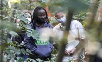 Climate activists Vanessa Nakate from Uganda and Leonie Bremer of the German Fridays for Future movement, right, visit activists in a forest near the Garzweiler open-cast coal mine in Keyenberg, western Germany, Saturday Oct. 9, 2021. Garzweiler, operated by utility giant RWE, has become a focus of protests by people who want Germany to stop extracting and burning coal as soon as possible. (AP Photo/Martin Meissner)