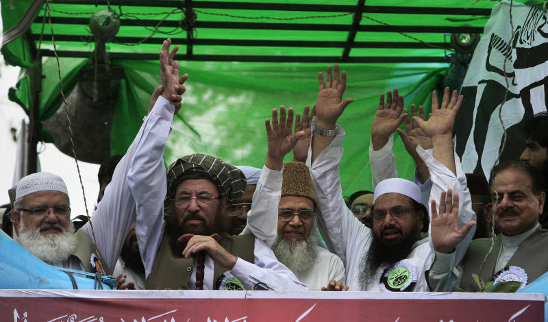 Maulana Samiul Haq, second left, head of a coalition of hardline Islamist religious leaders and politicians 'Defense of Pakistan Council', along with other coalition leaders wave to supporters as they lead a rally, in Lahore, Pakistan, Sunday, July 8, 2012. Prominent hardline Islamists led thousands of people in a protest against Pakistan's decision to allow the U.S. and other NATO countries to resume shipping troop supplies through the country to Afghanistan. (AP Photo/K.M. Chaudary)