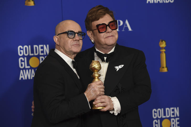 "Elton John, right, and Bernie Taupin pose in the press room with the award for best original score in a motion picture for ""I'm Gonna Love Me Again"" from ""Rocketman"" at the 77th annual Golden Globe Awards at the Beverly Hilton Hotel on Sunday, Jan. 5, 2020, in Beverly Hills, Calif. (AP Photo/Chris Pizzello)"