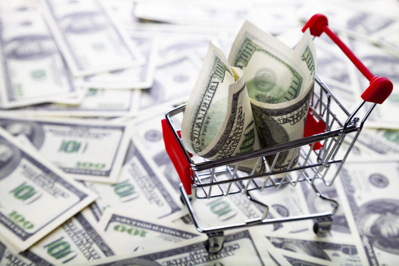 Tiny shopping cart with a hundred dollar bill in it on top of a pile of hundred dollar bills