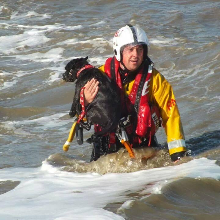 Undated handout photo issued by RNLI of crewman Darren Priestnall with dog Archie, who sparked a dramatic rescue operation after he fell from a cliff edge into the sea at Walton Backwaters in Essex. PRESS ASSOCIATION Photo. Issue date: Tuesday September 23, 2014. The inshore lifeboat from Harwich lifeboat station was on its way back from a fundraising event when it was contacted by Thames Coastguard during the incident earlier this month, an RNLI spokesman said. See PA story RESCUE Dog. Photo credit should read: RNLI/Keith Churchman/PA Wire  NOTE TO EDITORS: This handout photo may only be used in for editorial reporting purposes for the contemporaneous illustration of events, things or the people in the image or facts mentioned in the caption. Reuse of the picture may require further permission from the copyright holder.