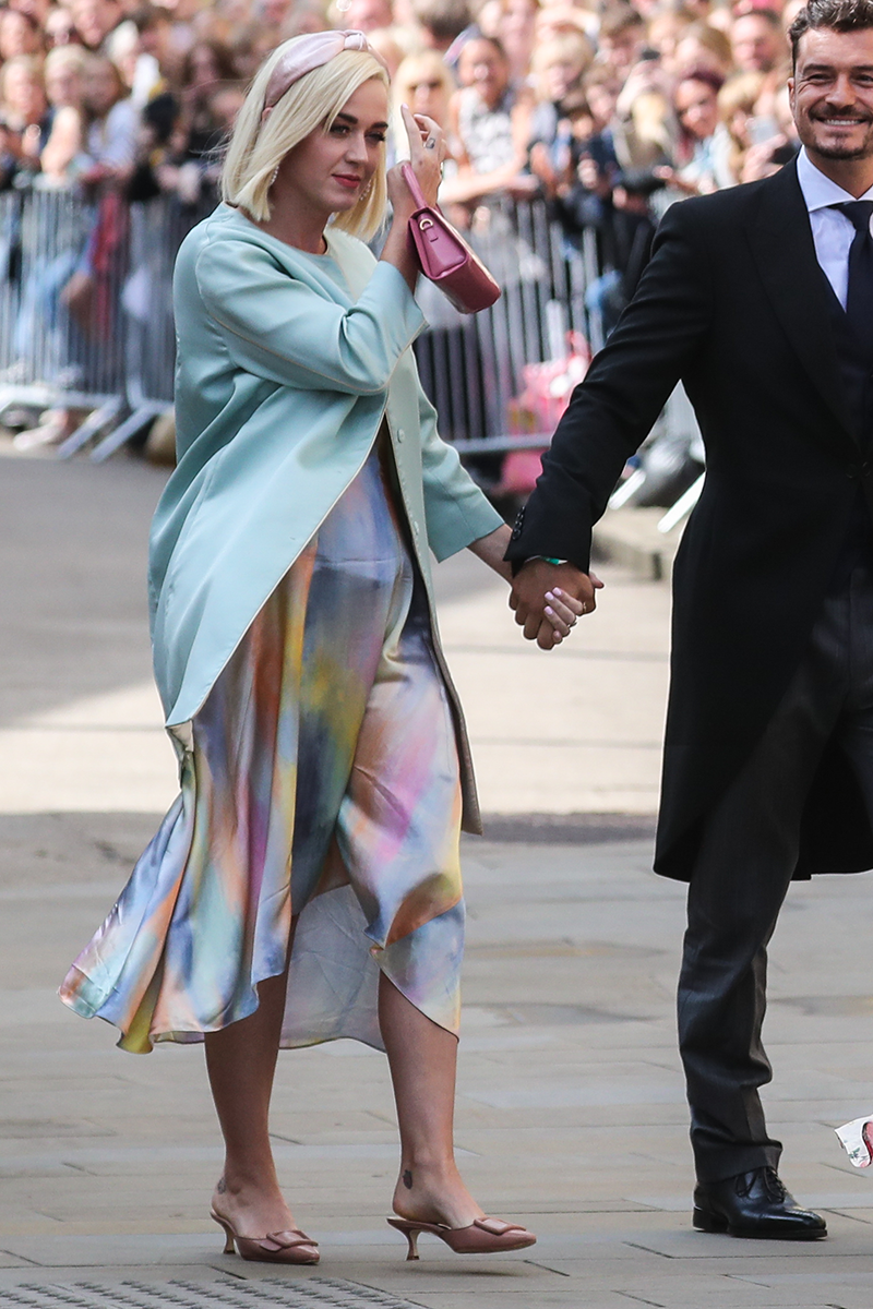 <p>Katy Perry looks radiant in this pastel watercolour-inspired midi worn under a powder blue coat with complementary accessories for Ellie Goulding's wedding.</p>