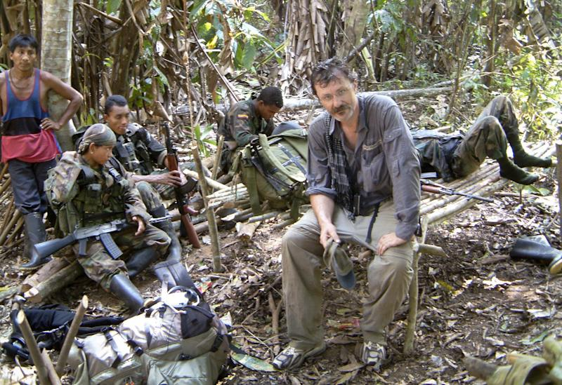 In this photo taken in 2003 and released by Robert Young Pelton on Tuesday, Nov. 5, 2013, Pelton sits in the presence of United Self-Defense Forces of Colombia (AUC) paramilitary members during a crossing of the Darien Gap, Colombia. Adventurer Robert Young Pelton, whose crowd-funding scheme has already drawn criticism from a pair of Africa experts, is the latest to join a line of private individuals and aid groups who are trying to corner Joseph Kony and the members of his Lord's Resistance Army. (AP Photo/Robert Young Pelton) EDITORIAL USE ONLY