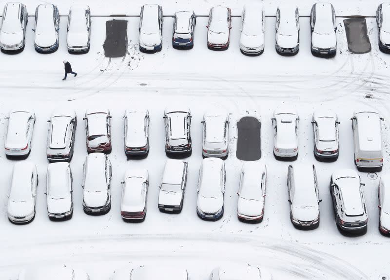 A person walks past cars covered with snow in the parking lot in Saint Petersburg