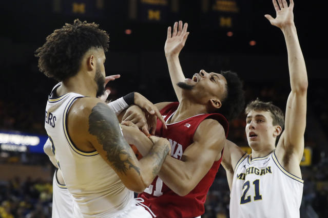 Indiana forward Jerome Hunter, center, and Michigan forward Isaiah Livers, left, fight for the rebound during the first half of an NCAA college basketball game, Sunday, Feb. 16, 2020, in Ann Arbor, Mich. (AP Photo/Carlos Osorio)